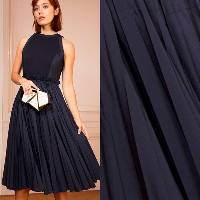Midnight blue dress with sharply tailored bodice and fluid, pleated skirt
